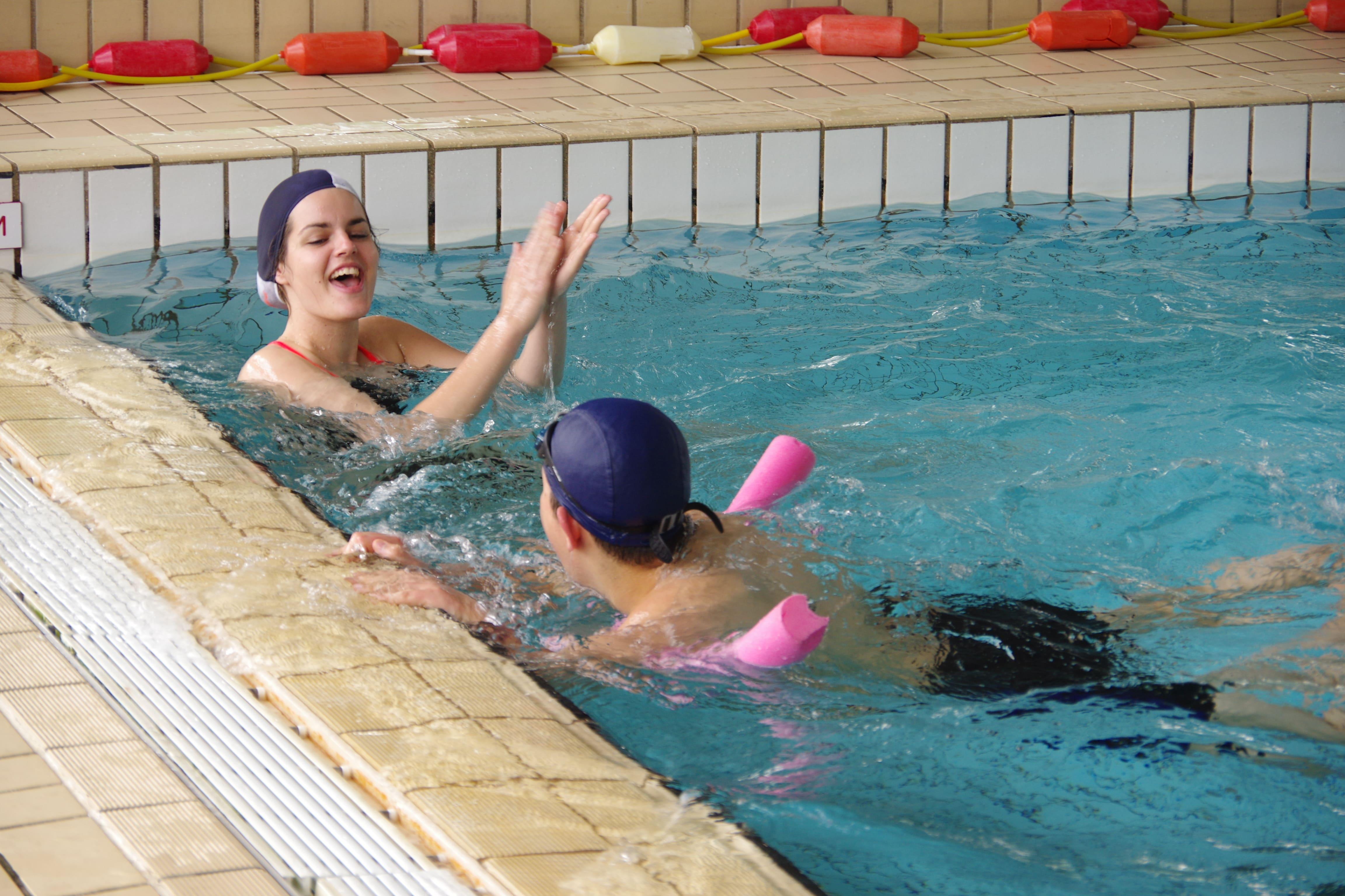 bénévole en train d'applaudir un jeune pendant l'activité piscine