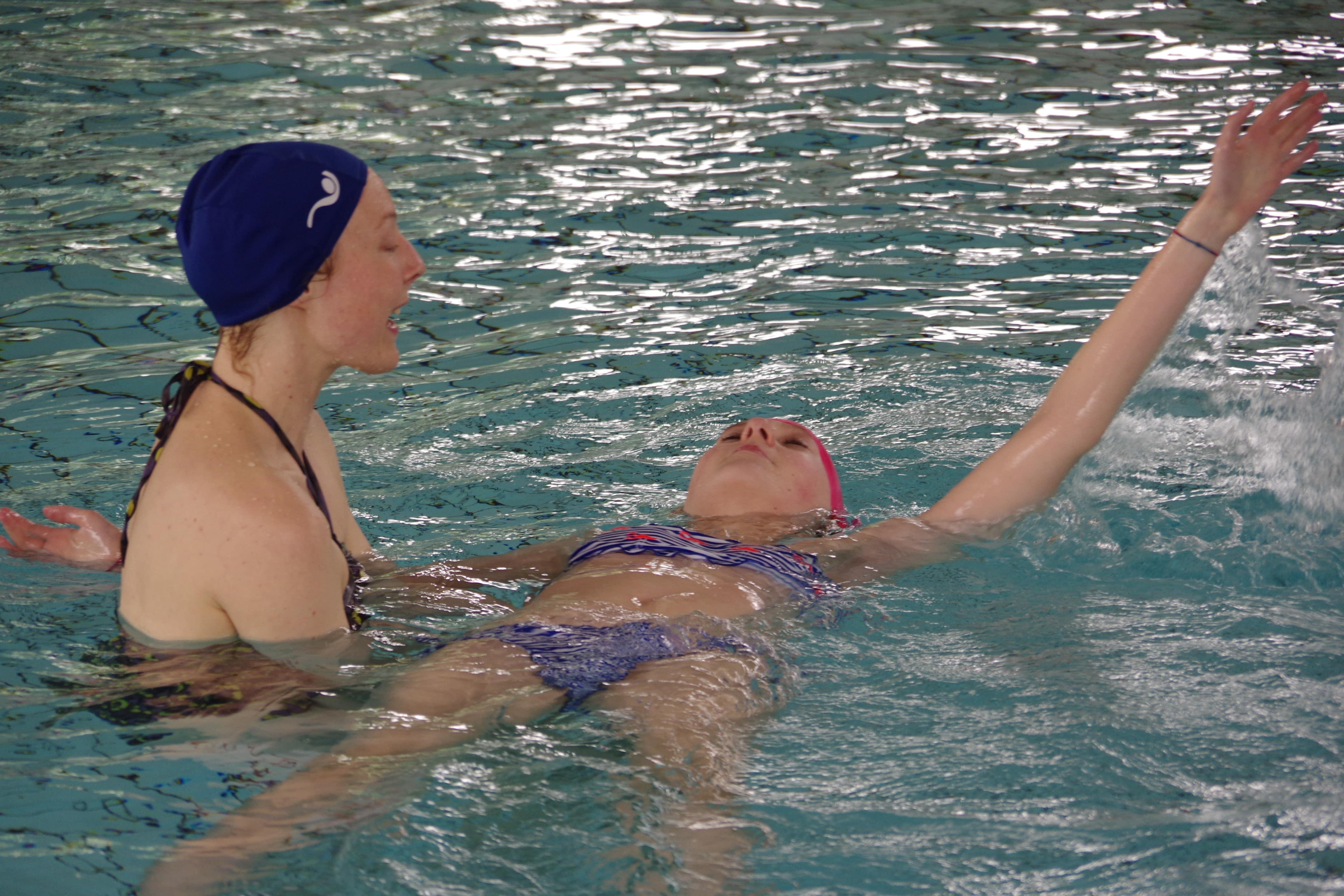 bénévole en train d'aider une enfant à nager