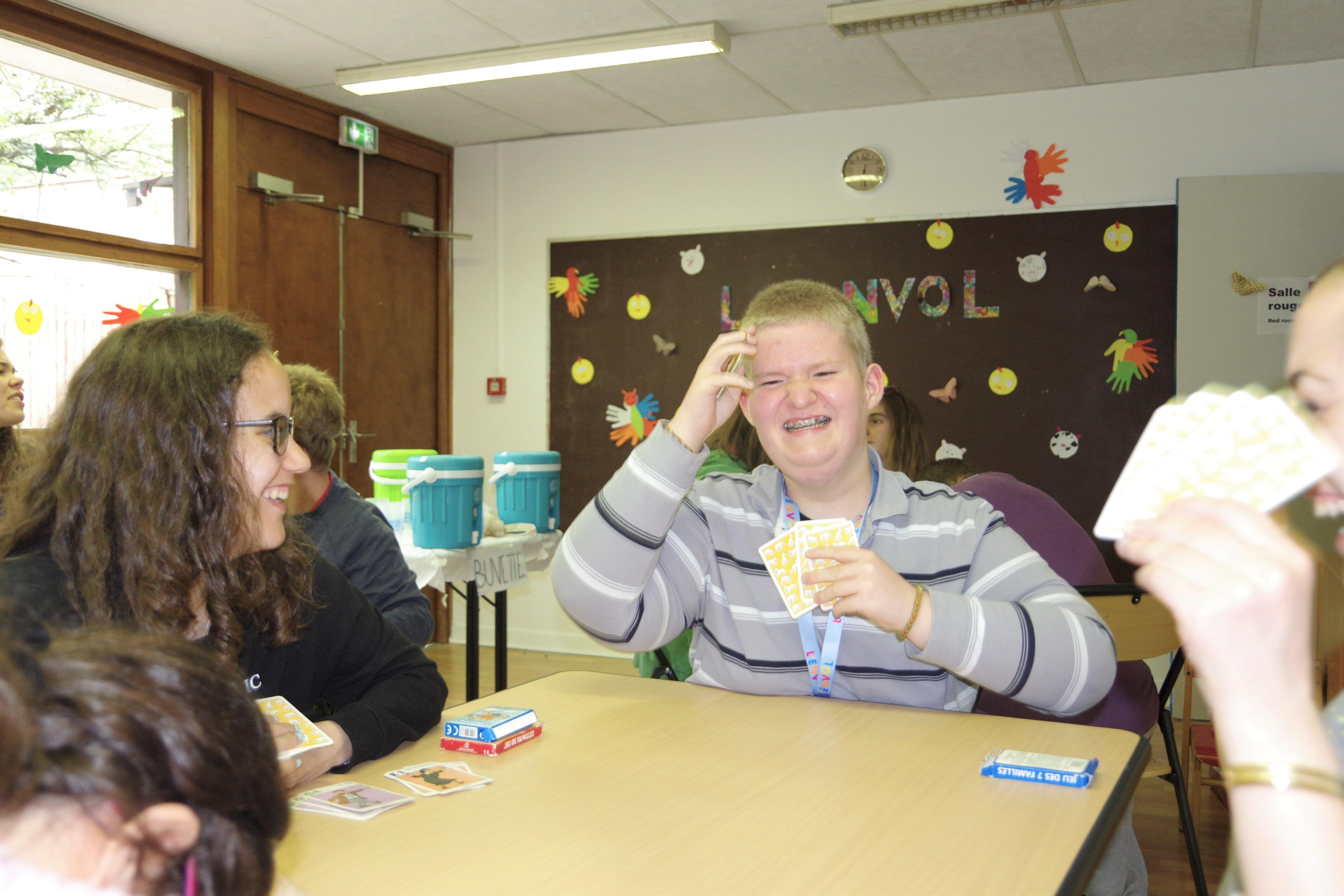 enfants et bénévoles en train de rire en jouant aux cartes