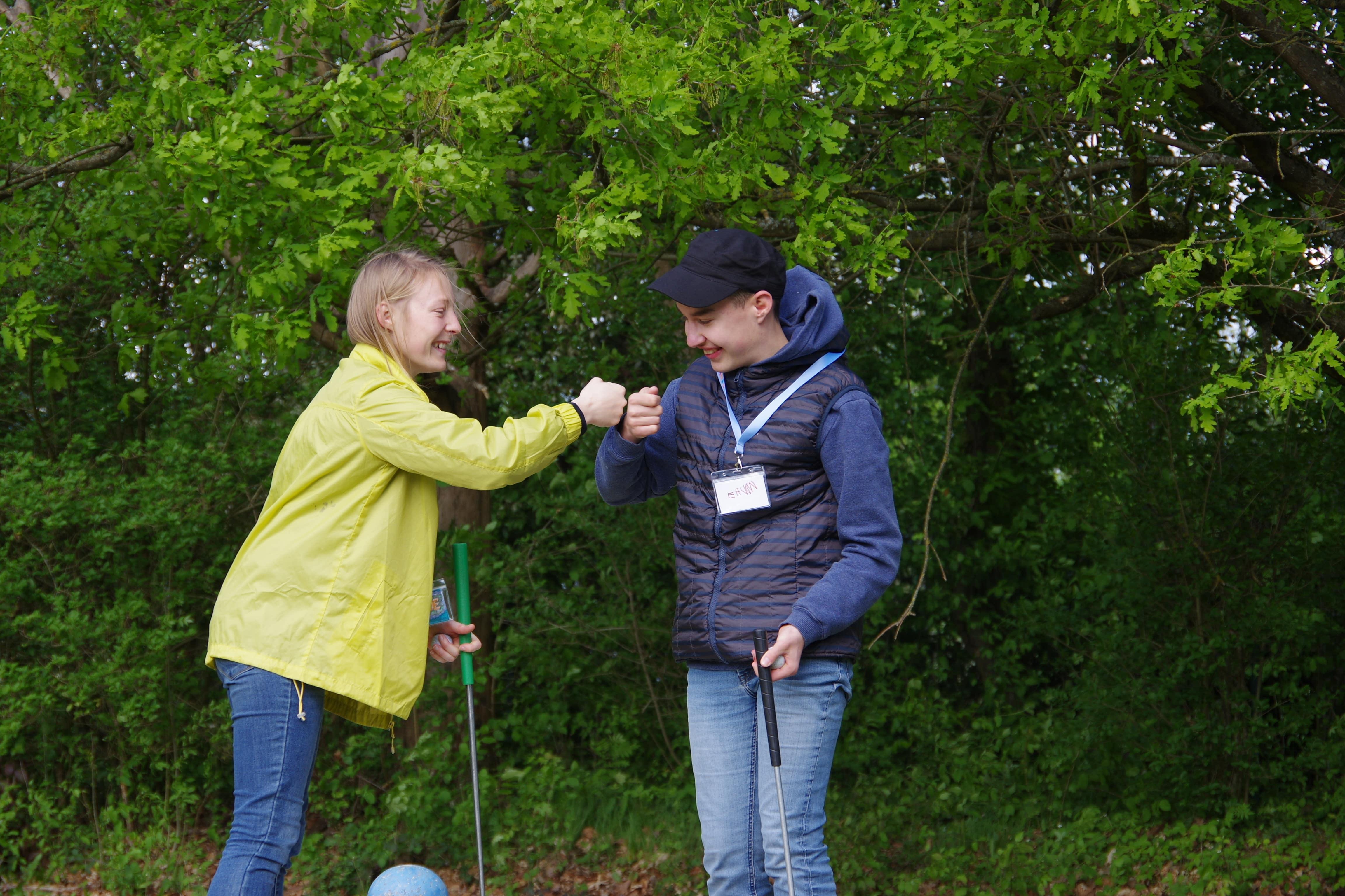 enfant et bénévole se tapant dans les mains pendant les jeux extérieurs