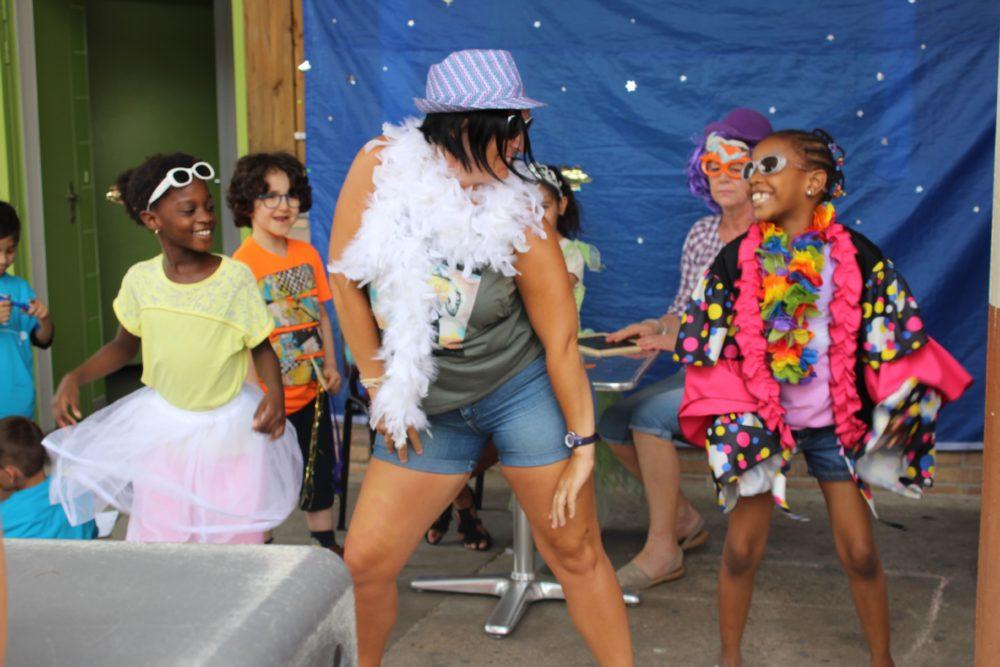 Bénévole et enfants déguisés en train de danser