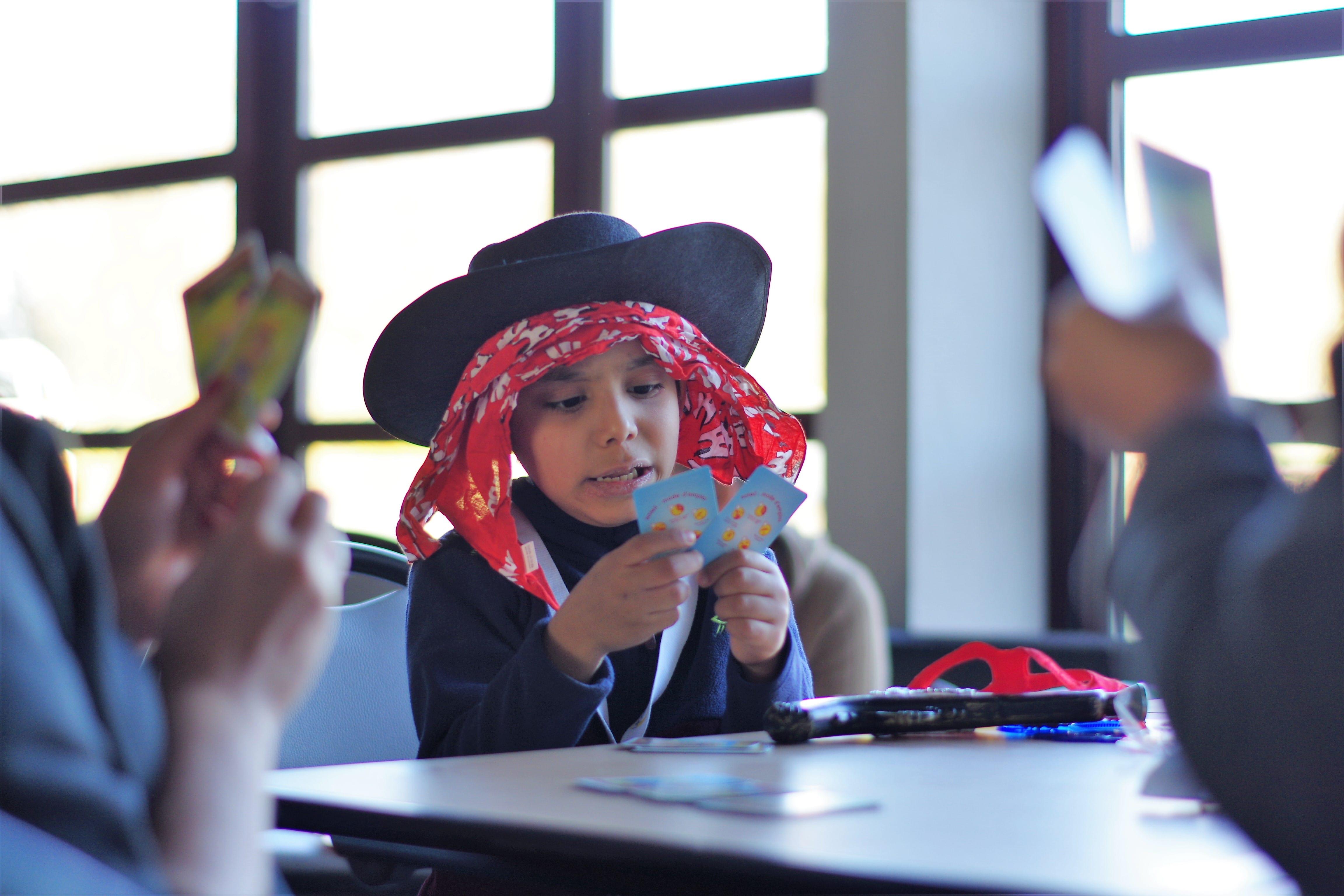 Enfant déguisé jouant aux cartes