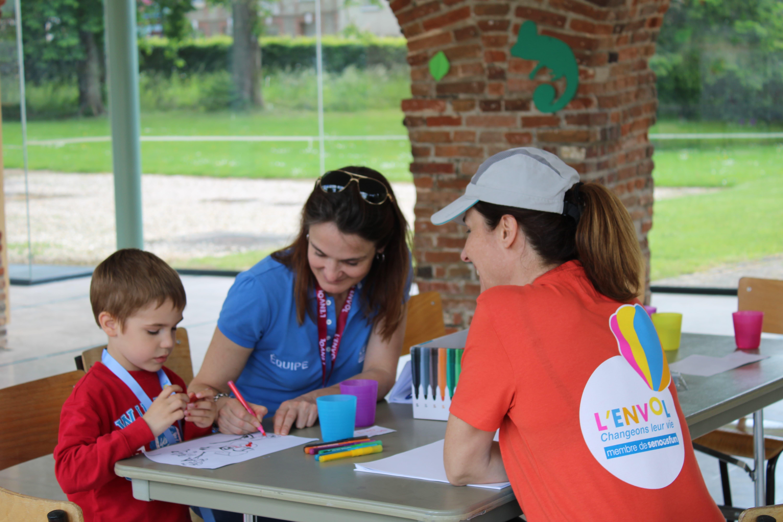 Enfant et bénévoles en train de dessiner