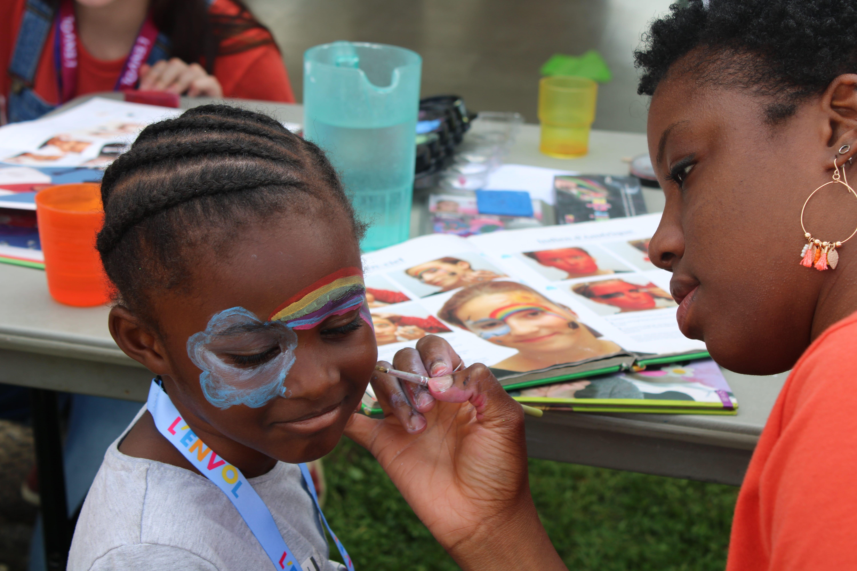 Enfant en train de se faire maquiller par une bénévole