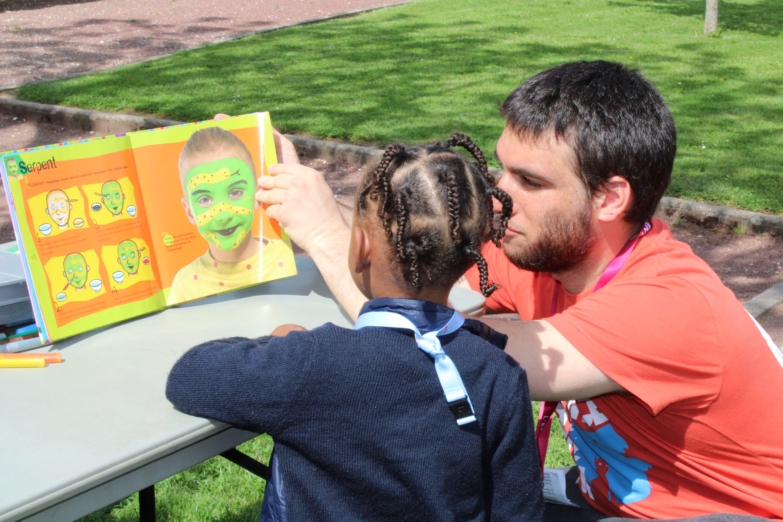 Enfant et bénévole choisissant un maquillage