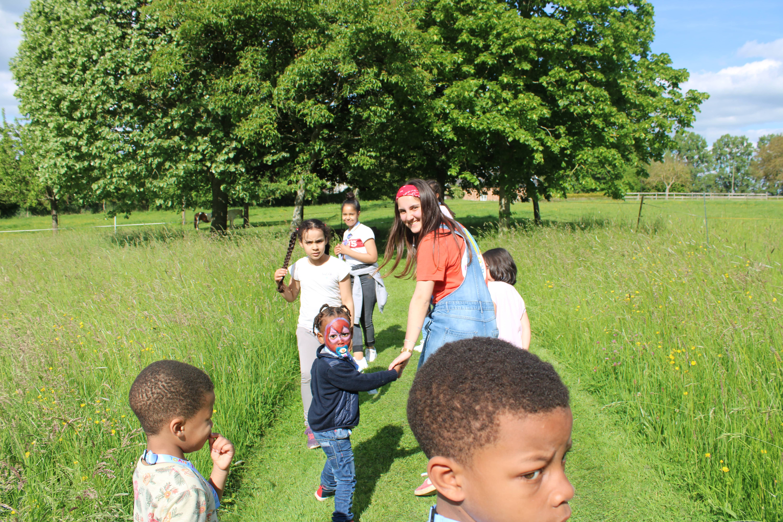 Enfants et bénévole allant voir la mini-ferme