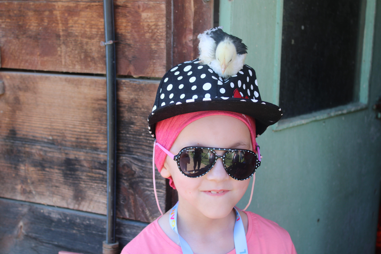Enfant avec un poussin sur la tête