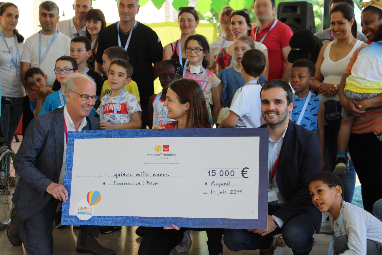 Familles, partenaires et équipe L'ENVOL posant avec le chèque géant de Malakoff Médéric Humanis