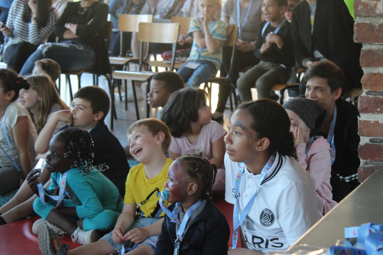 Enfants riant devant le spectacle de bienvenue