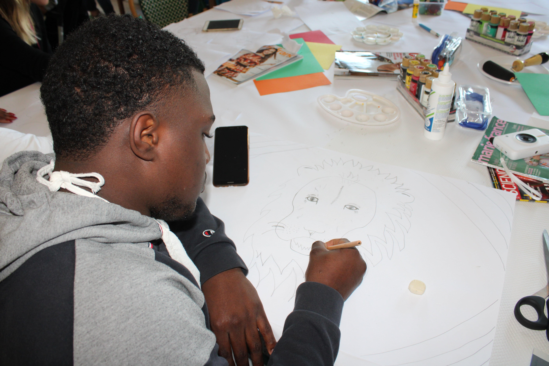 Jeune dessinant son animal totem pendant l'activité arts créatifs