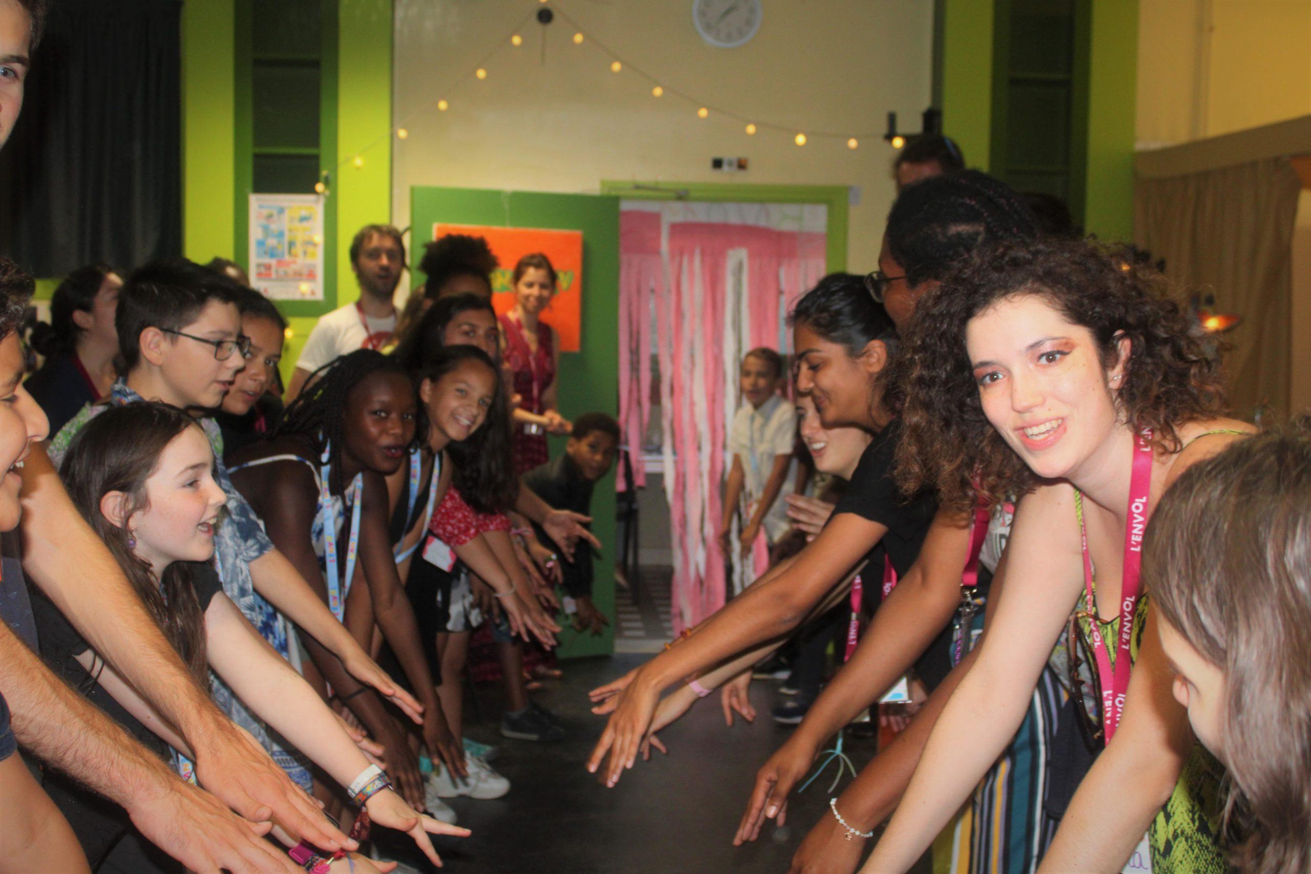 Enfants et bénévoles de L'ENVOL qui font la olà